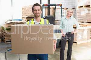 Smiling warehouse worker carrying box