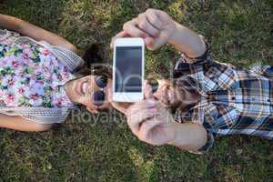Young couple lying on grass taking selfie