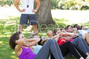 Fitness group doing sit ups in park with coach