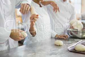 Colleagues holding rolling pin and dough