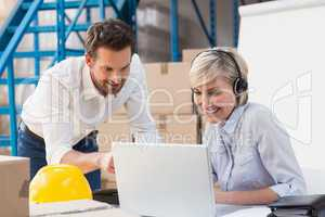 Warehouse managers using laptop and wearing headset