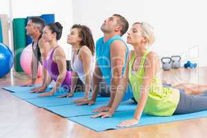 People doing yoga stretch in gym class