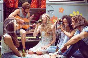 Hipster friends by camper van at festival