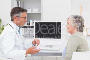 Male doctor conversing with senior patient at table