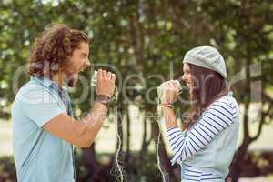 Young couple shouting through tin cans
