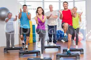 People performing step aerobics exercise in gym