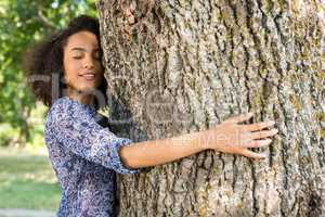 Pretty young woman hugging a tree