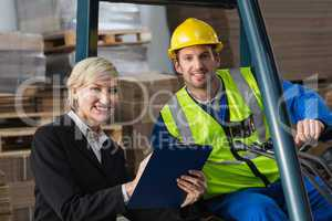 Forklift driver and manager smiling at camera