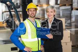 Forklift driver and his manager smiling at camera