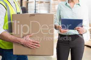 Worker carrying box with manager holding tablet pc