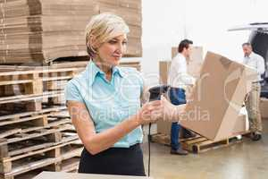 Smiling warehouse manager scanning package