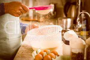 Woman sieving flour into bowl