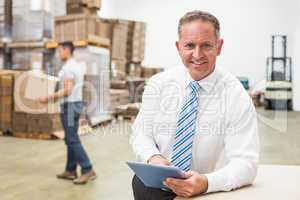 Boss using digital tablet in warehouse