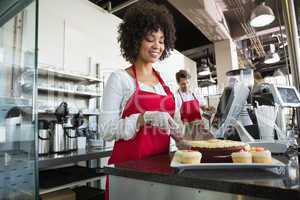 Beautiful waitress in red apron slicing cake