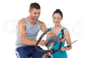 Trainer with client on exercise bike