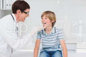 Doctor examining a little boy with stem