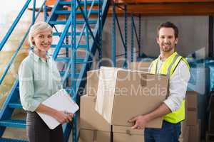 Worker holding box with manager holding clipboard