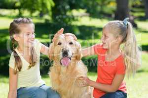 Sister petting their dog in the park