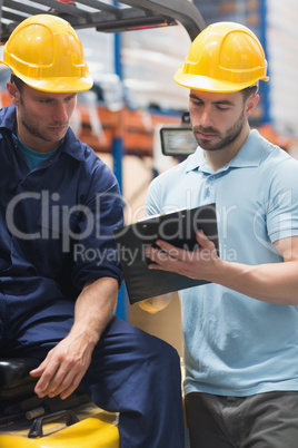 Focused warehouse workers talking together