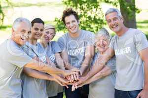 Happy volunteer family putting their hands together
