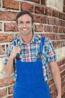 Composite image of confident plumber holding tool over white bac