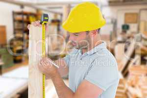Composite image of carpenter using measure tape to mark on woode
