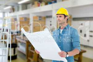 Composite image of architect holding blueprint in house