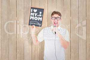Composite image of geeky hipster holding blackboard and singing