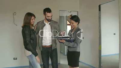 Real Estate Agent Saleswoman With Clients Customers Buying New House