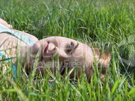 Young sensual smiling blonde lying on the grass in the sunlight