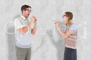 Composite image of geeky hipster couple speaking with tin can ph