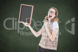 Composite image of geeky hipster woman holding blackboard and si