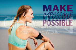 Composite image of fit woman sitting on the beach taking a break