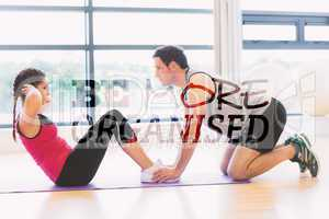 Composite image of trainer helping woman do abdominal crunches i