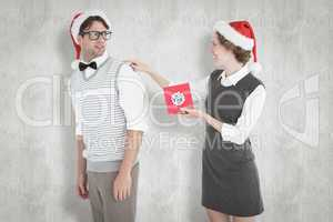 Composite image of geeky hipster offering present to her boyfrie