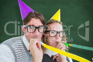 Composite image of geeky hipster couple blowing party horn