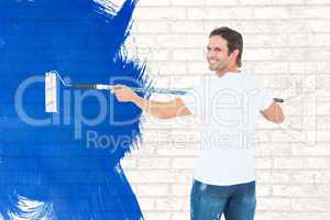 Composite image of happy man using paint roller