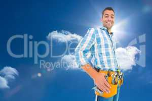Composite image of portrait of smiling handyman wearing tool bel