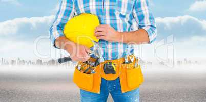 Composite image of manual worker wearing tool belt while holding