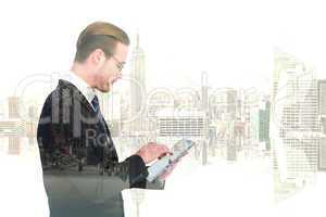 Composite image of businessman in reading glasses using his tabl