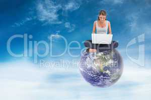 Composite image of cross-legged woman using a laptop