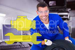 Composite image of portrait of happy mechanic working on tire
