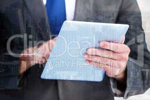 Composite image of businessman scrolling on his digital tablet