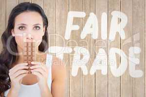 Composite image of pretty brunette eating bar of chocolate