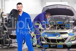 Composite image of smiling male mechanic holding tire