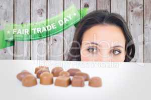 Composite image of pretty brunette peeking at chocolate