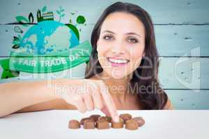 Composite image of pretty brunette picking out chocolate