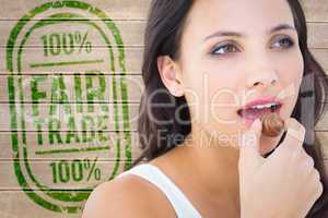 Composite image of pretty brunette eating chocolate candy