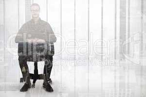 Composite image of stern businessman sitting on an office chair