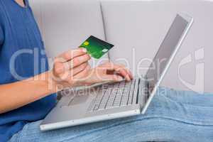 Woman doing online shopping with laptop and credit card